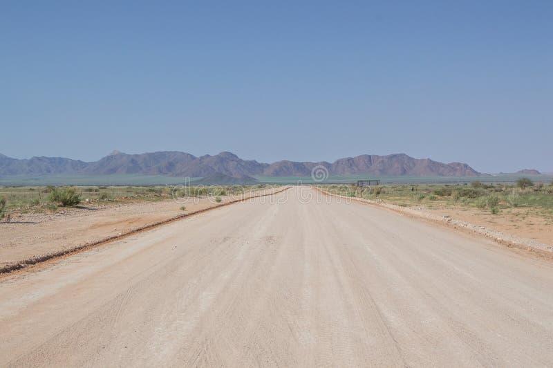 Estrada da estrada de terra em uma paisagem do deserto com as montanhas em Namíbia imagens de stock royalty free
