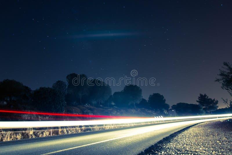 Estrada da montanha da noite com fugas do carro imagem de stock