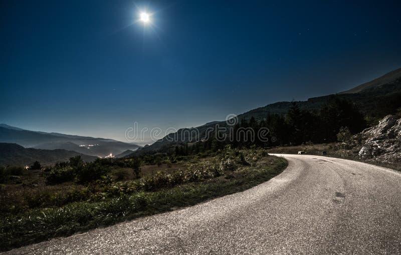 Estrada da montanha na noite com Lua cheia imagem de stock