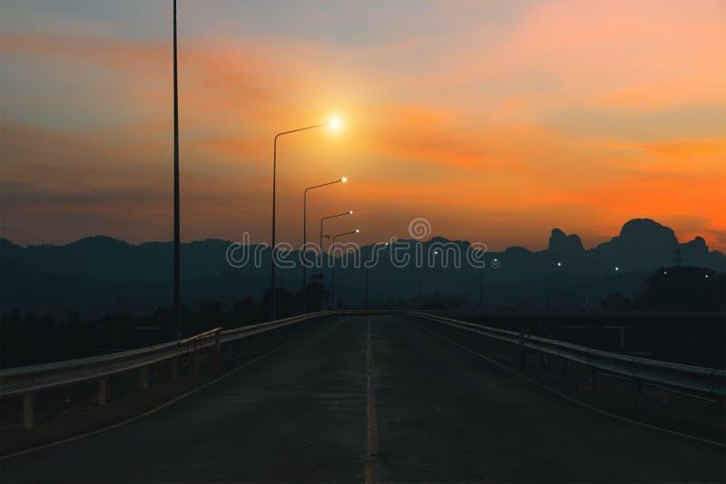 Estrada da montanha Paisagem de surpresa com as rochas, o c?u do por do sol e a estrada asfaltada indo ao horizonte na noite Aven fotos de stock