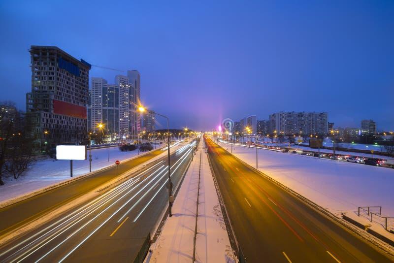 Estrada da noite na cidade com carro que a luz arrasta imagens de stock royalty free