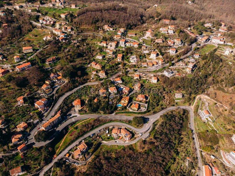 Estrada de enrolamento da montanha às curvaturas, às casas com o telhado vermelho telhado, à piscina e à garagem Vista superior a fotos de stock