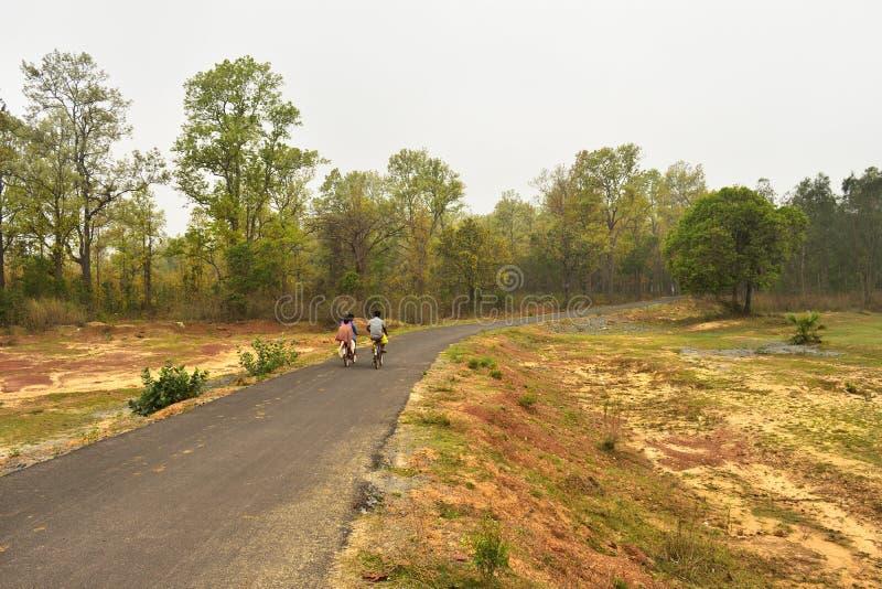 Estrada de enrolamento do cascalho através da floresta temperada em Jhargram, bengal ocidental, Índia foto de stock