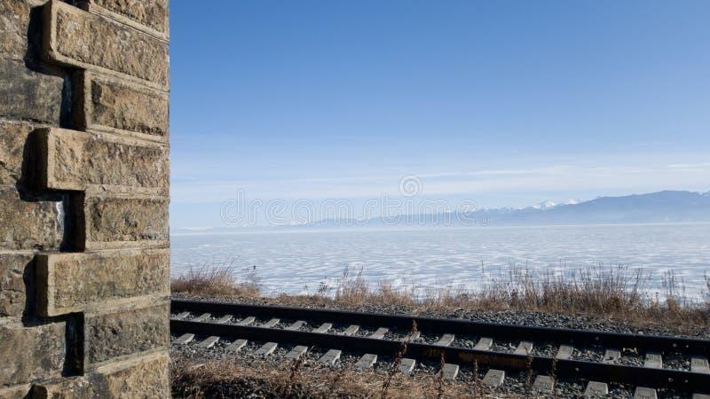 Estrada de ferro de Circum-Baikal no inverno e na mola O Lago Baikal no gelo, trilhos, peça da parede velha do túnel no quadro fotografia de stock