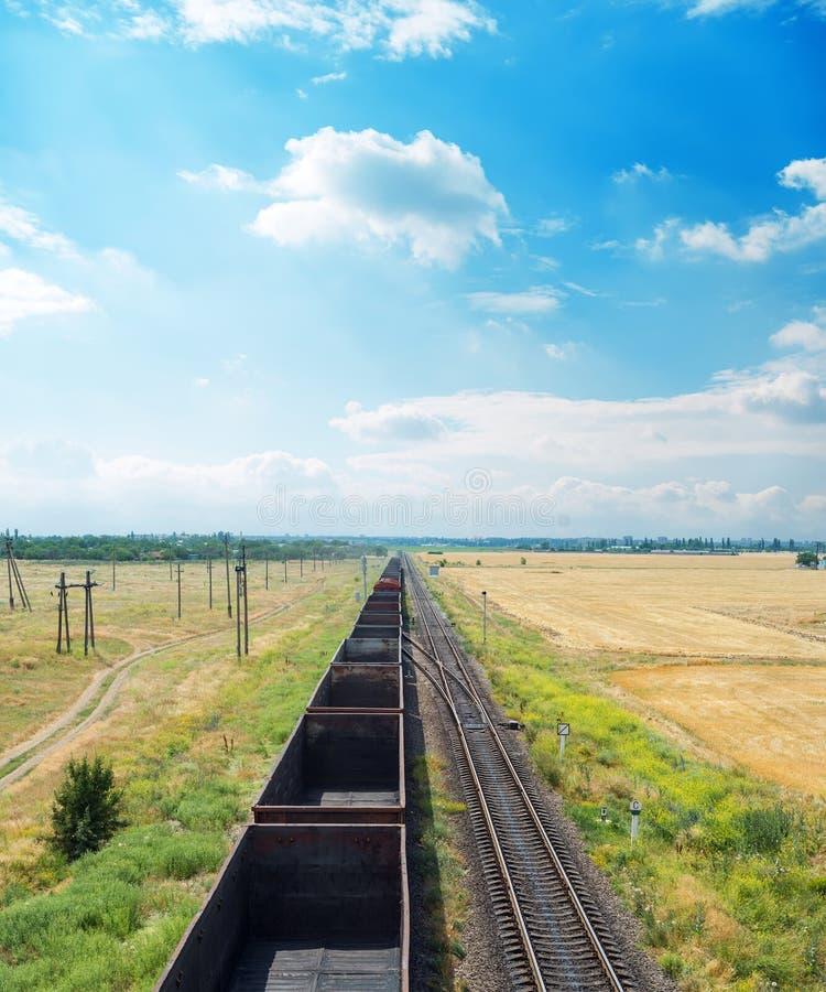 estrada de ferro com vagões vazios e o céu azul com nuvens fotografia de stock