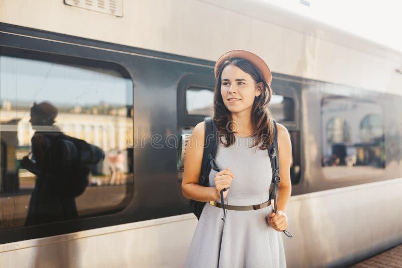 Estrada de ferro e curso do tema Mulher caucasiano nova do retrato com o sorriso toothy que está no fundo do trem do estação de c imagem de stock royalty free