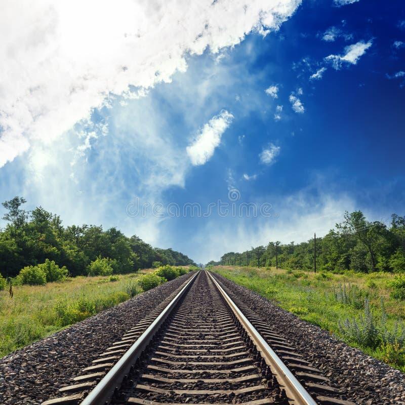 estrada de ferro na paisagem verde ao horizonte no céu azul com nuvens imagens de stock
