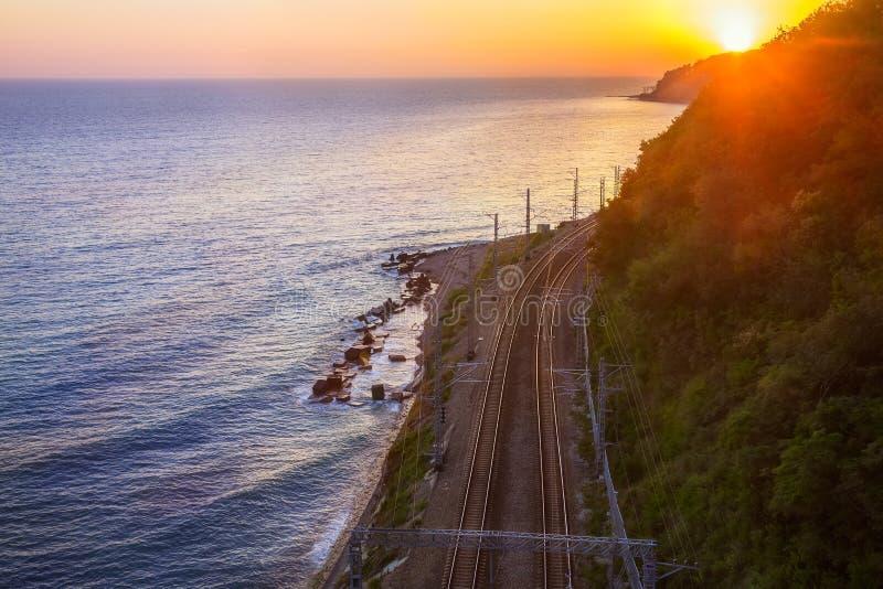 Estrada de ferro nas folhas do seacoast no por do sol fotos de stock