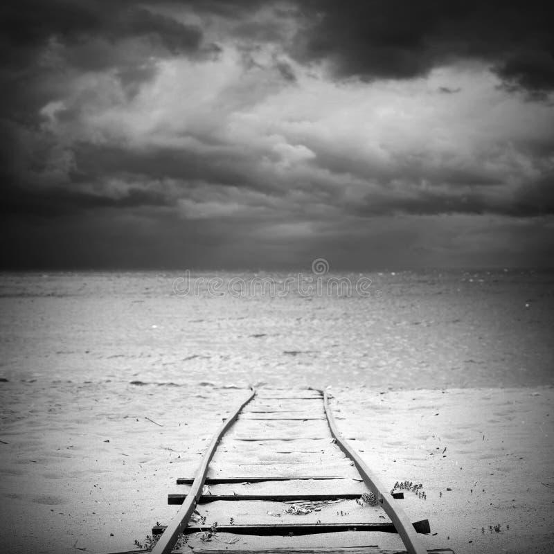 A estrada de ferro velha vai sobre o Sandy Beach à água do mar fotos de stock royalty free