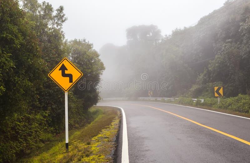 Estrada de floresta ventosa com um sinal da curva em um dia nevoento em Doi Intha fotografia de stock royalty free