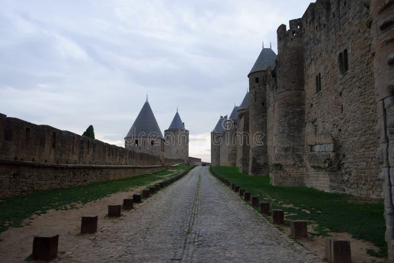 A estrada de pedra entre as paredes e as torres do castelo de Carcassonne imagens de stock