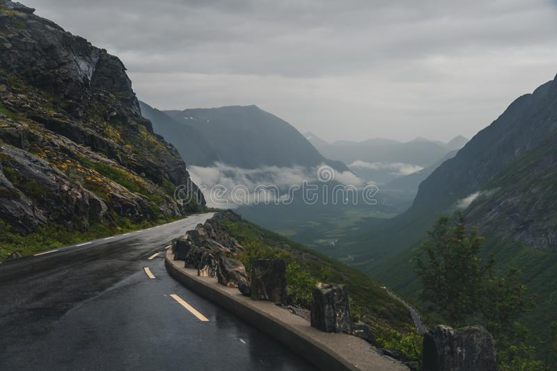 Estrada de serpentina nas montanhas da Noruega, Trollstigen, escada de troll, clima sombrio, asfalto úmido imagem de stock