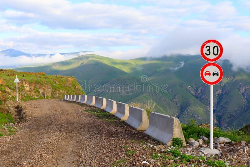 Estrada de terra ao longo da borda dos sinais do penhasco e de estrada no vale das montanhas da altura do monte Região de Sagarej foto de stock