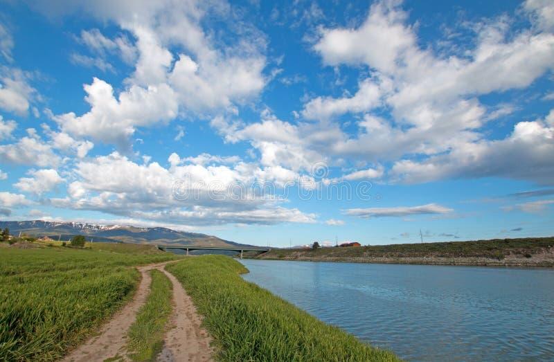 Estrada de terra do país ao longo do rio Snake sob o céu da nuvem de cúmulo em Wyoming alpino imagem de stock royalty free