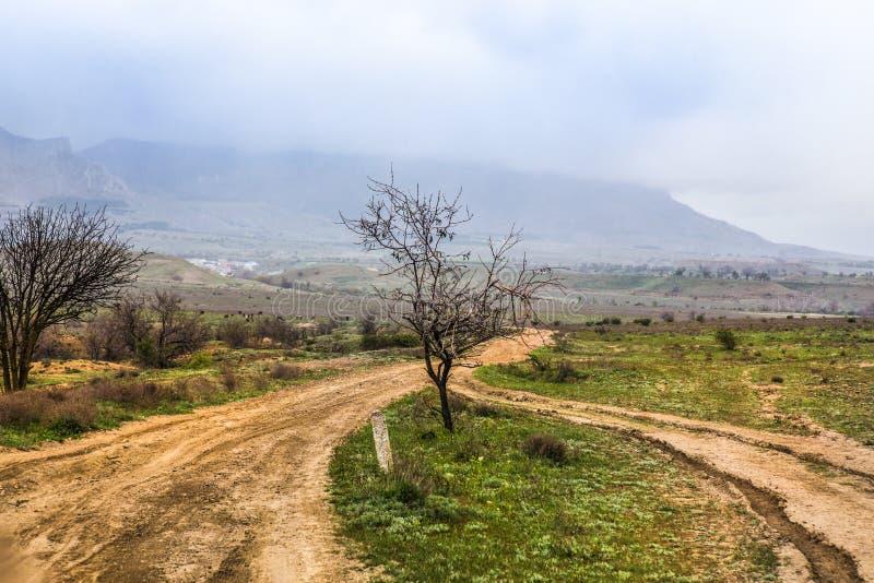 estrada de terra e montanhas na névoa imagens de stock
