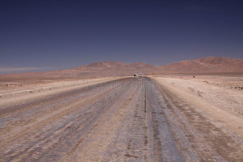 Estrada de terra infinita à infinidade do platô liso de sal que contrasta com o céu sem nuvens azul foto de stock royalty free