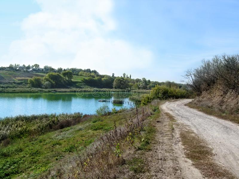 Estrada de terra perto de uma lagoa pequena na região de Sumy da vila de Ugroidy, Ucrânia Pescando o cais no lago, no pântano e n imagem de stock royalty free