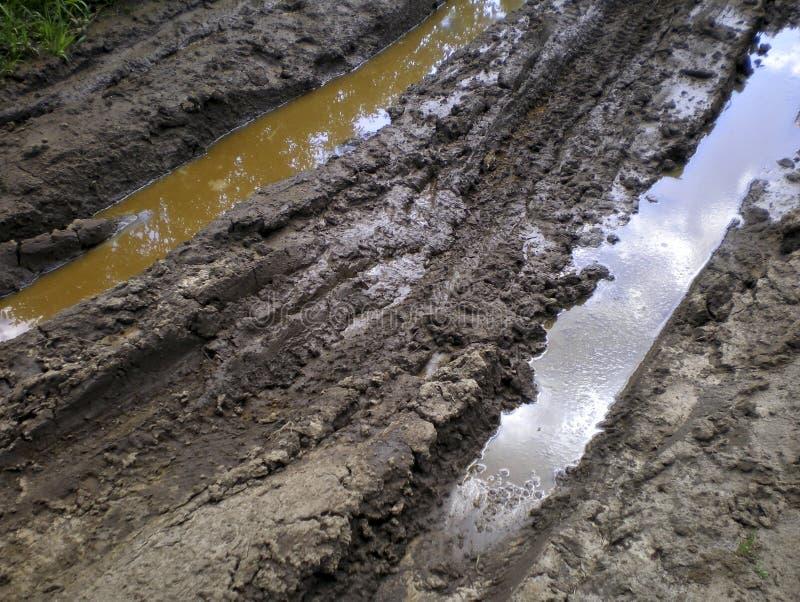 estrada de terra Rotina-enchida com poças imagem de stock