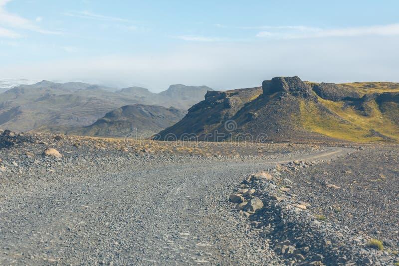 Estrada do cascalho através das montanhas islandêsas da lava fotografia de stock