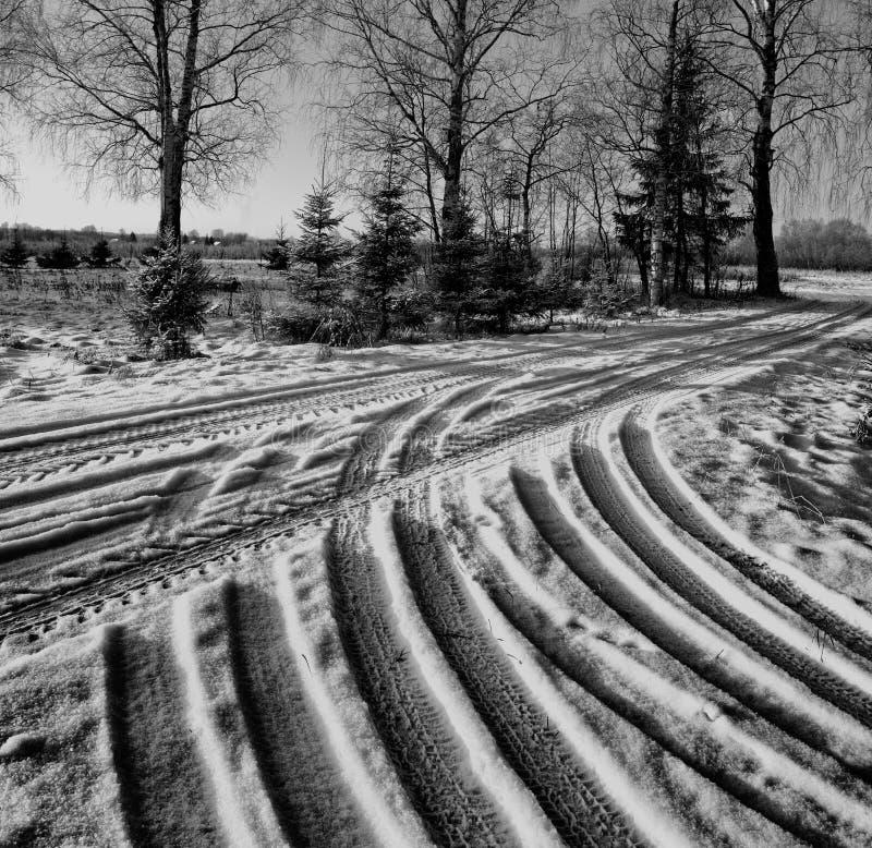 Estrada do inverno com traços de passo do pneu de carro imagem de stock