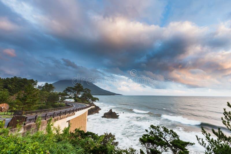 Estrada do litoral com Mt Kaimon no por do sol, Kagoshima, Japão fotografia de stock royalty free