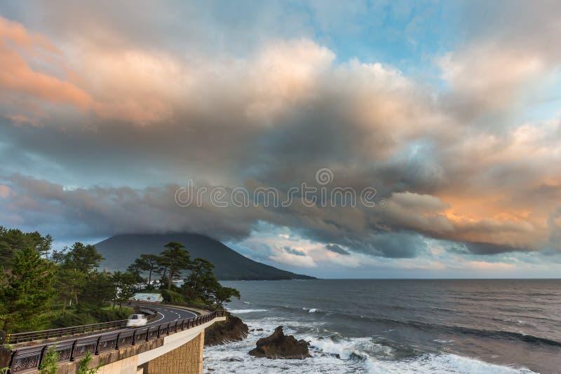 Estrada do litoral com Mt Kaimon no por do sol, Kagoshima, Japão foto de stock
