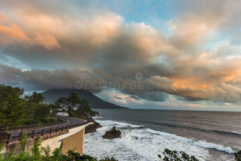 Estrada do litoral com Mt Kaimon no por do sol, Kagoshima, Japão fotografia de stock