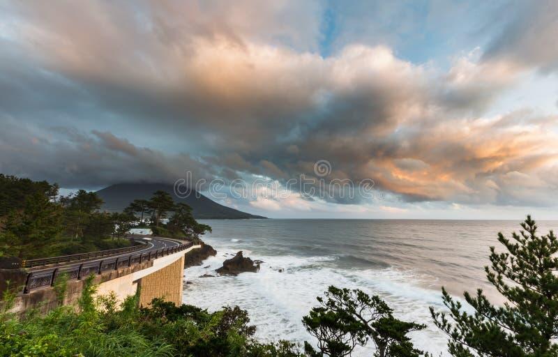 Estrada do litoral com Mt Vulcão de Kaimon no por do sol bonito, Kago imagem de stock