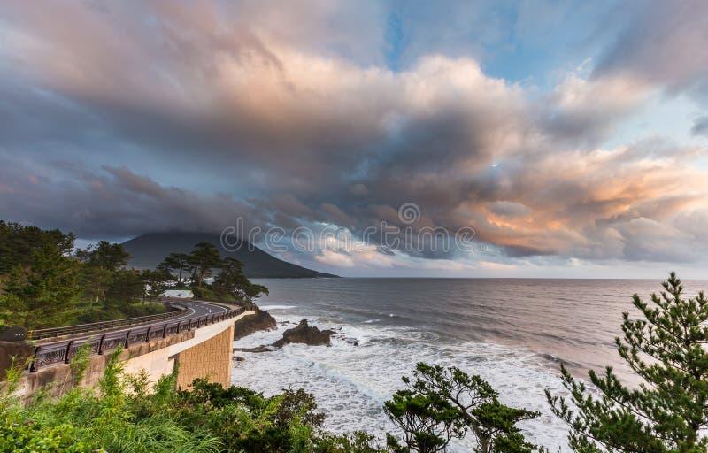 Estrada do litoral com Mt Vulcão no por do sol bonito, Kagoshima de Kaimon, Kyushu, Japão imagens de stock royalty free