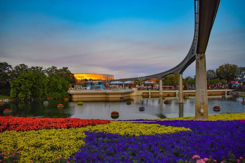Estrada do monotrilho, flores coloridas e lago no fundo do por do sol em Epcot em Walt Disney World fotos de stock royalty free