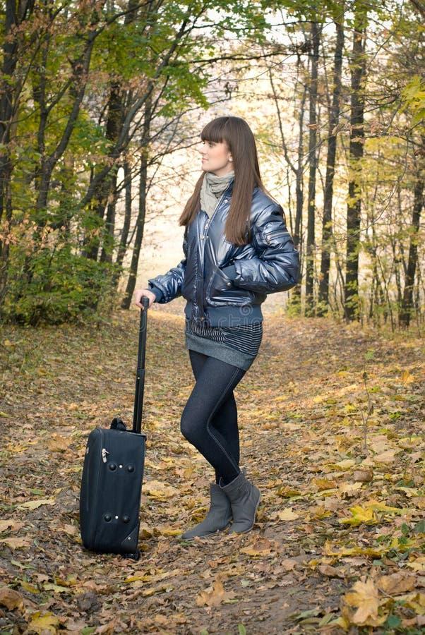 Estrada do outono: Menina com mala de viagem. imagens de stock