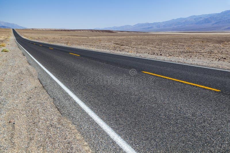 Estrada do Vale da Morte em linha reta através do deserto às montanhas na distância imagens de stock