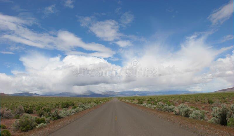 Estrada e céus nebulosos adiante imagem de stock
