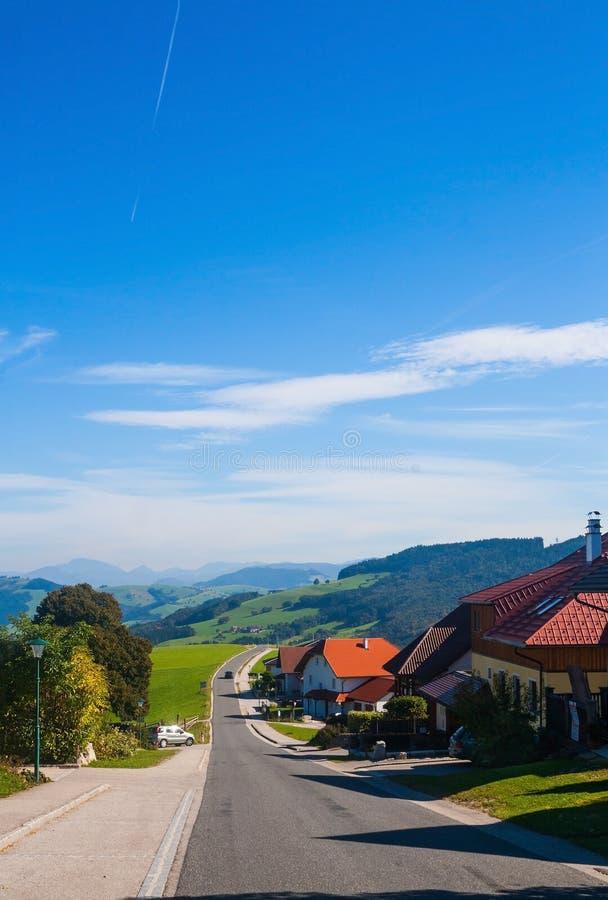 Estrada e casas nos cumes austríacos foto de stock