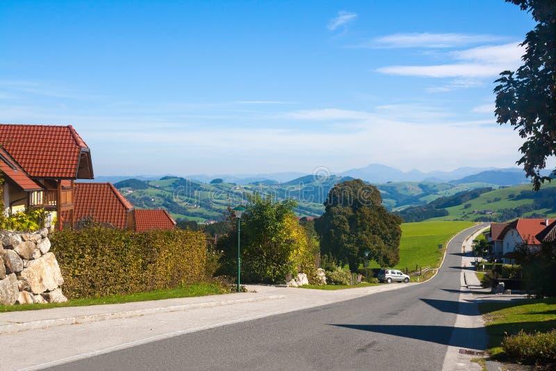 Estrada e casas nos cumes austríacos imagem de stock