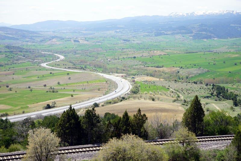 Estrada e estrada de ferro perto das montanhas nevado imagens de stock