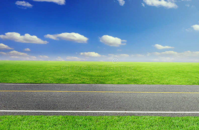 Estrada e grama nebulosa de céu e verde imagens de stock