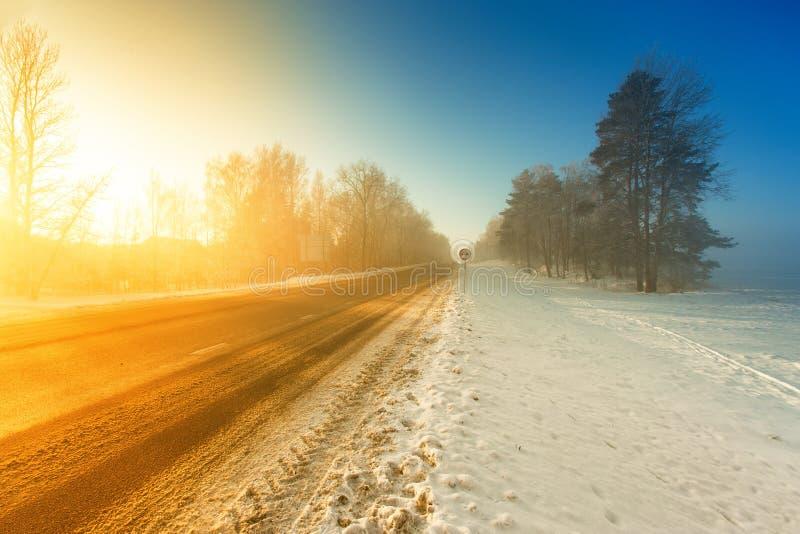 Estrada enevoada da estrada do inverno na luz solar da manhã imagens de stock