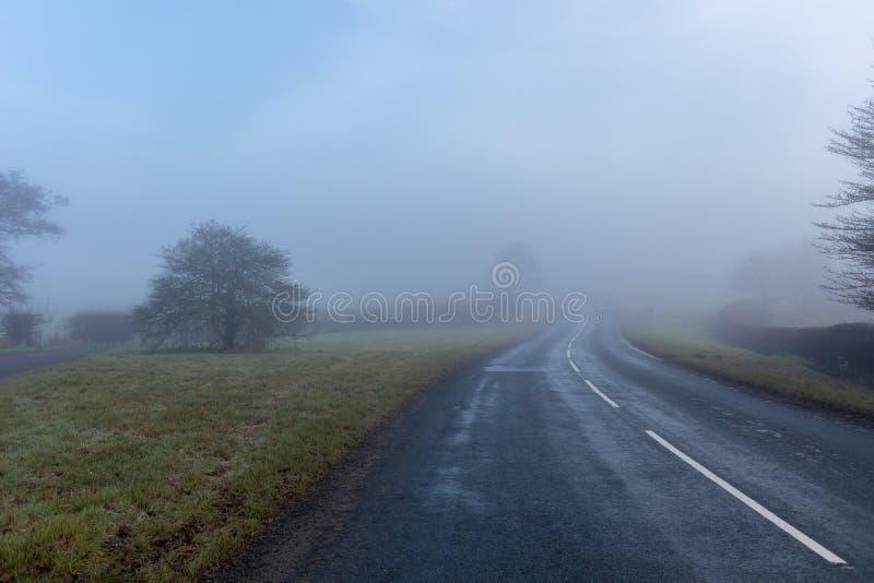 Estrada enevoada que conduz a em qualquer lugar fotografia de stock royalty free