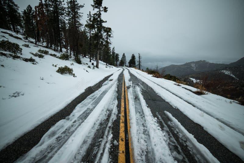Estrada escorregadiço uncleared perigosa do inverno do asfalto com neve nas montanhas imagem de stock royalty free