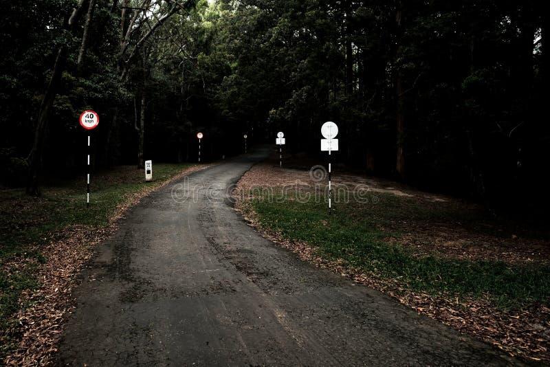 Estrada escura em ir acima em montes com sinais da velocidade da estrada fotografia de stock