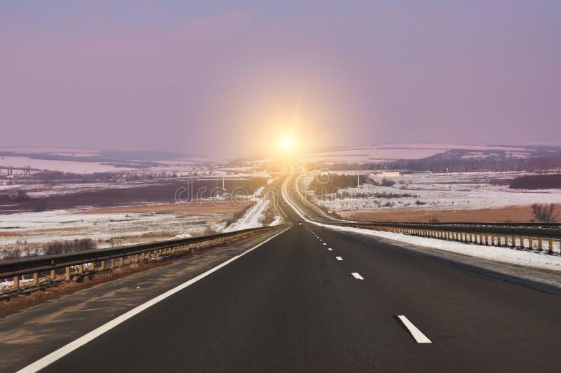 A estrada está apagando-se na distância entre os campos e os montes do inverno fotografia de stock
