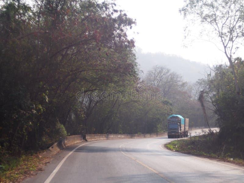 Estrada estreita rural só em terras tropicais com árvores e os montes verdes imagens de stock royalty free