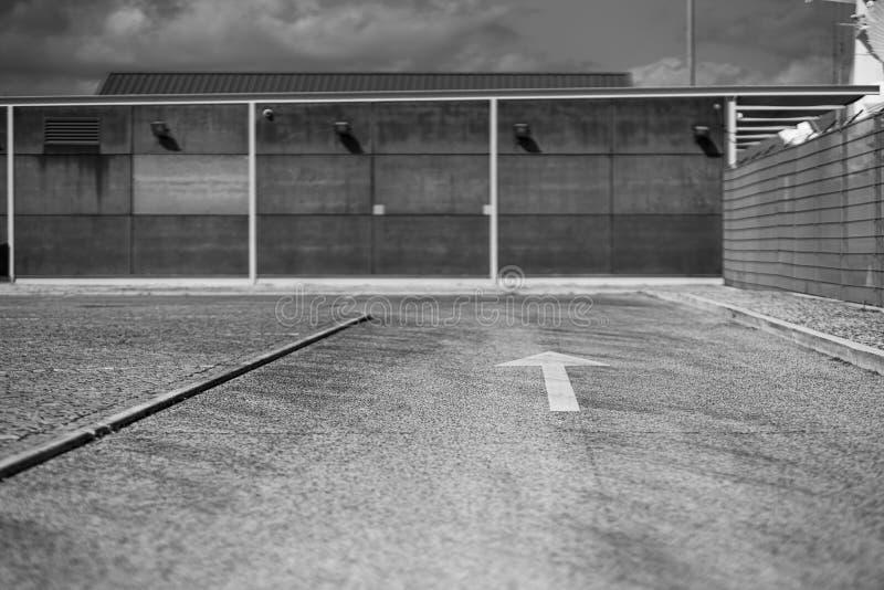 Estrada Greyscale com a seta nela fotos de stock