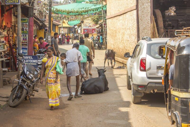 A estrada indiana na cidade e os pedestres contorneiam a vaca que encontra-se na estrada imagens de stock royalty free