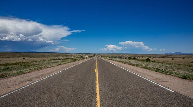 Estrada longa no deserto americano, céu azul com nuvens fotos de stock royalty free