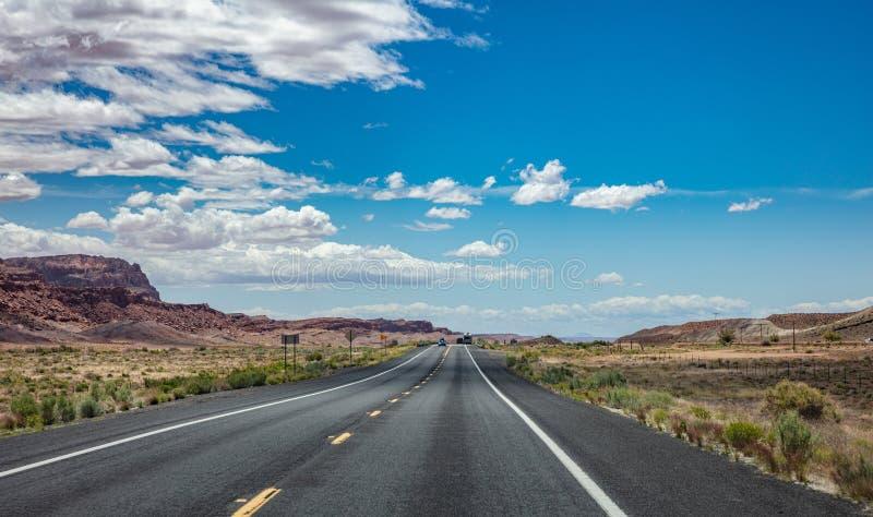 Estrada longa no deserto americano, fundo azul do céu nebuloso fotografia de stock royalty free