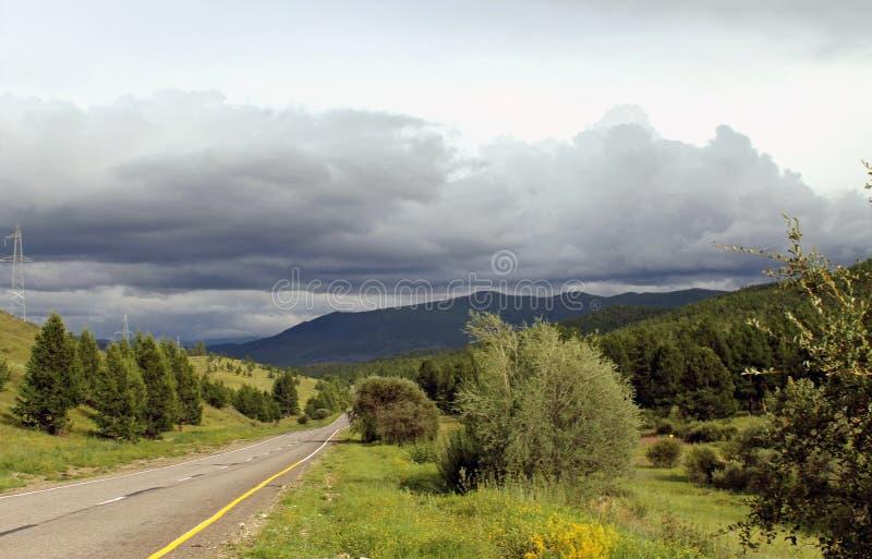 A estrada na floresta sob um céu azul com branco nubla-se montanhas de Sayan Sibéria Rússia imagem de stock