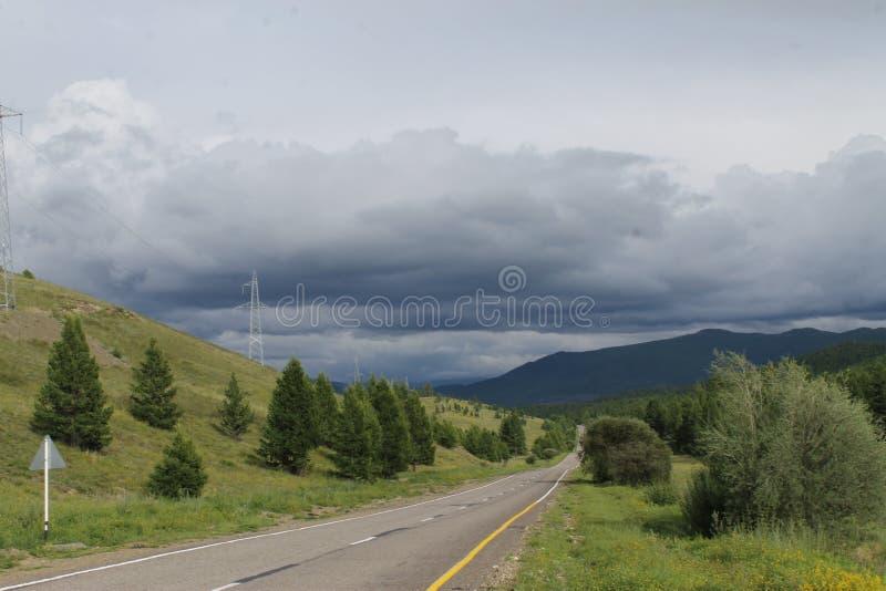 A estrada na floresta sob um céu azul com branco nubla-se montanhas de Sayan Sibéria Rússia imagens de stock