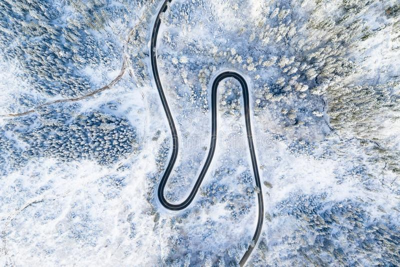 Estrada na opinião aérea da floresta do inverno Estrada de enrolamento sem os carros nas montanhas imagens de stock